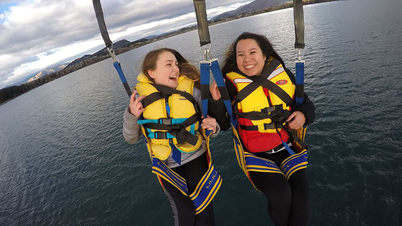 Shannon Kelly, left, parasails in New Zealand with a friend during her study abroad trip to Australia.