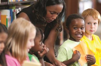 stock image of teacher with children from the website of the Illinois New Teacher Collaborative