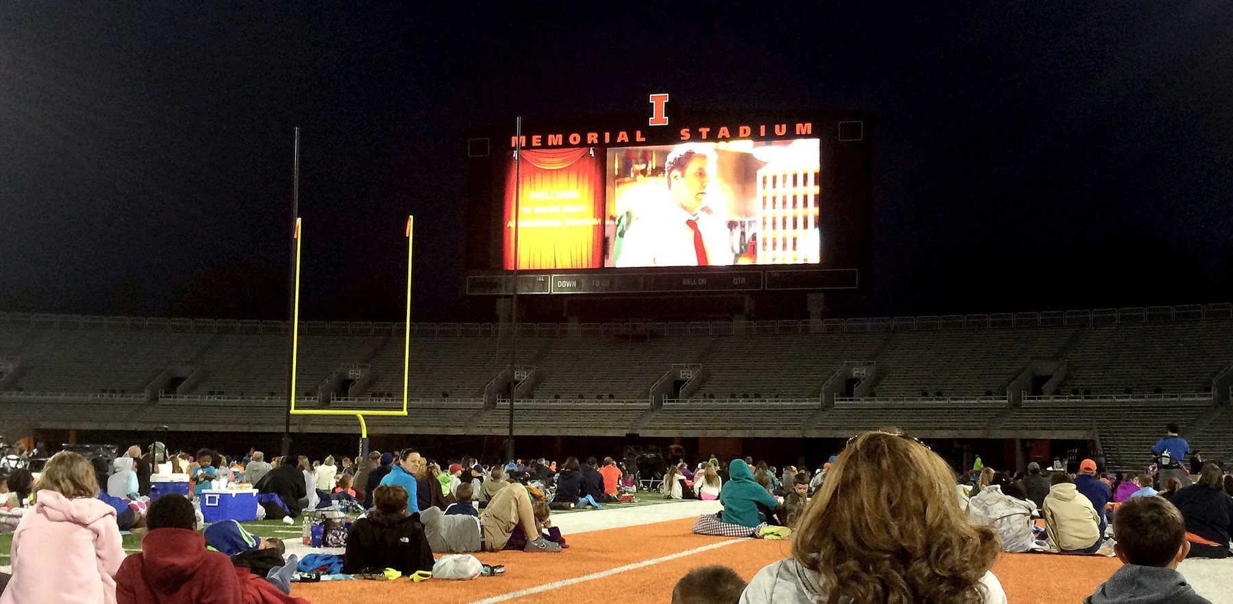 movie plays on the big screen at Memorial Stadium as fans relax on the field