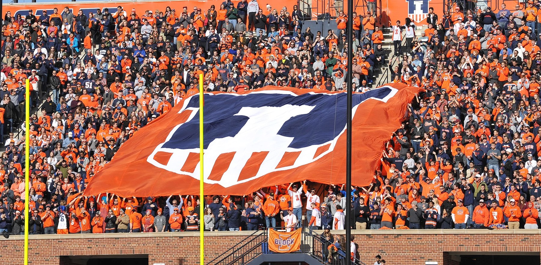 crowd at Memorial Stadium holding a huge 'Illini shield' banner
