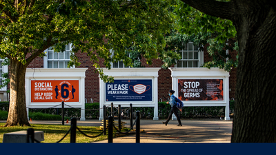 signs outside the Illini Union display safety messages - wear a mask, socially distance, wash your hands
