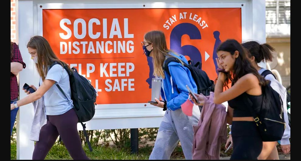 illinois students walk past signage for 'safe distancing.' Photo via the Associated Press