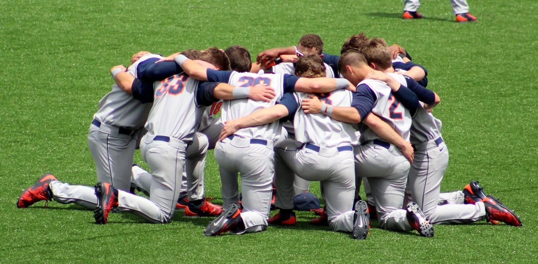 Illini baseball team members huddle on their knees