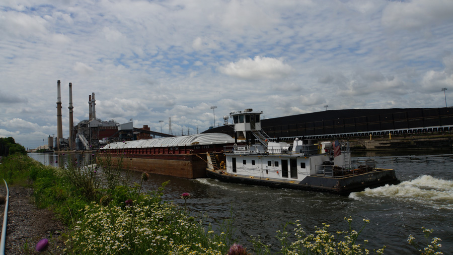A tugboat pushes a barge on the Chicago Sanitary and Ship Canal past a coal-fired electric power plant.