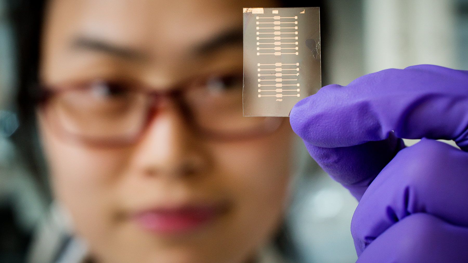 researcher looks at small plastic sensor that reacts to breath