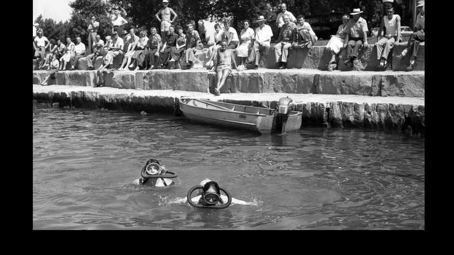 Volunteer divers Robert Domkowski, left, and Chuck Napravnik, right, search Lake Michigan for three missing bodies at Montrose Harbor after a meteotsunami hit the lakefront on June 26, 1954. (Chicago Tribune historical photo)