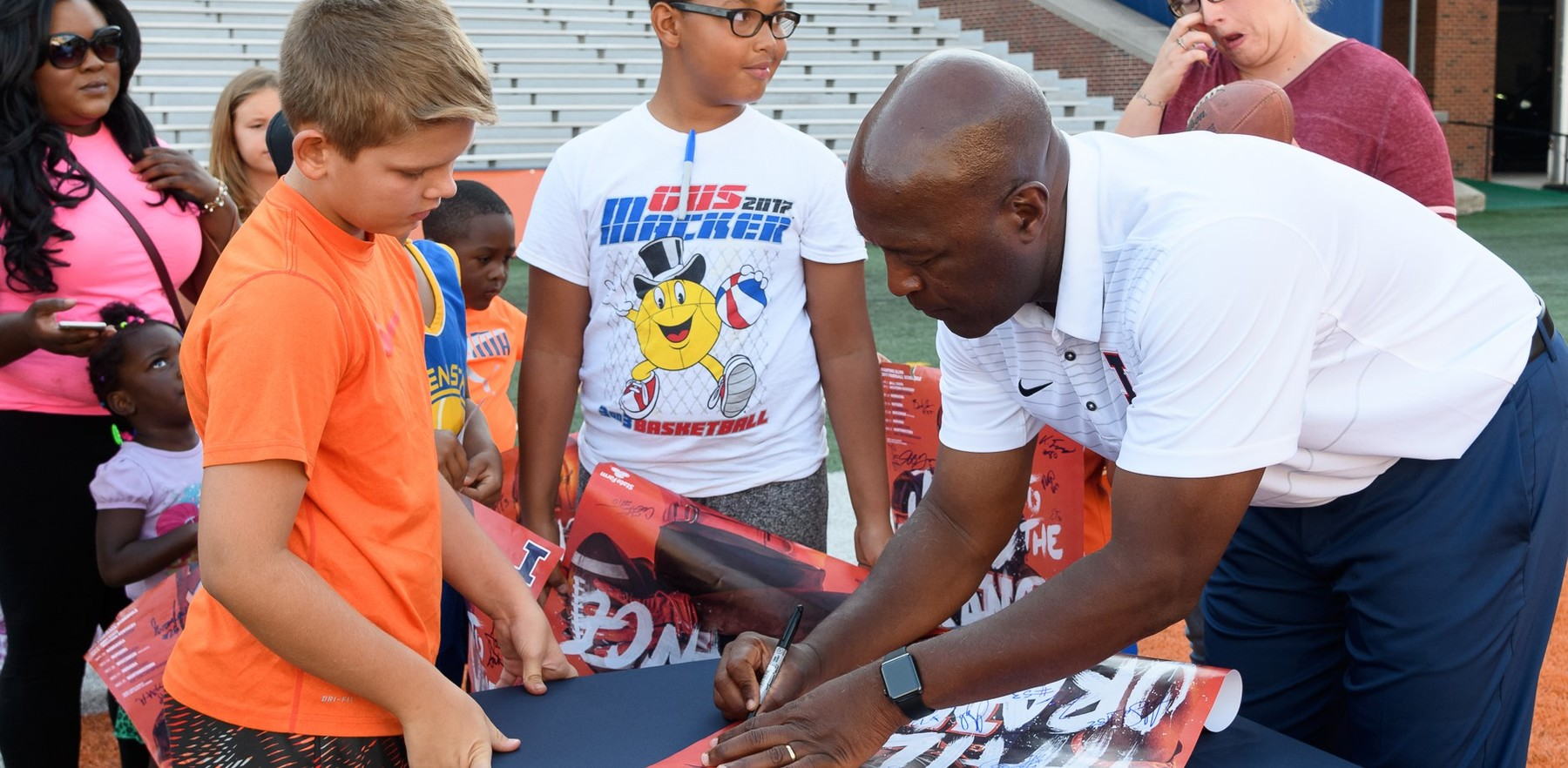 Coach Lovie Smith signs autographs for children