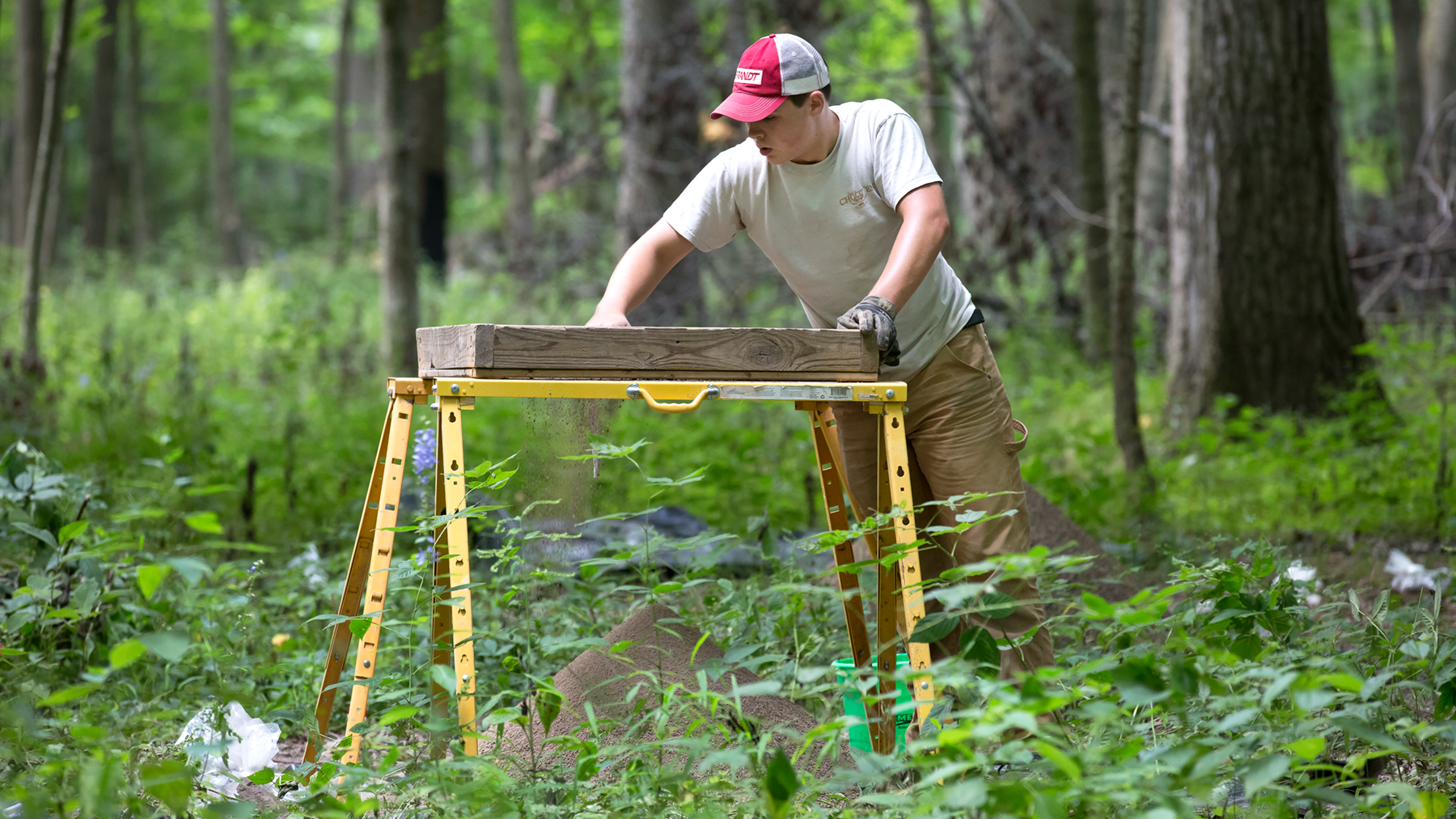 Parkland College student Kaleb Cotter sifts through materials uncovered in excavations of native mounds in Robert Allerton Park. Photo by L. B. Stauffer