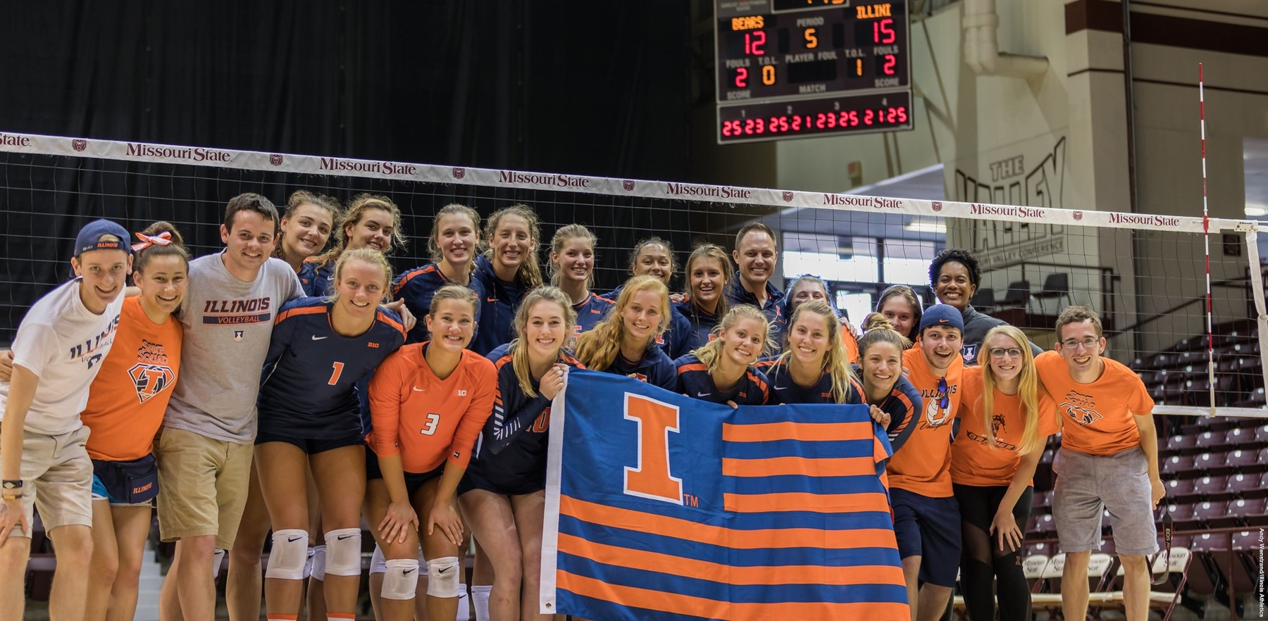 volleyball players and fans surround an Illini flag