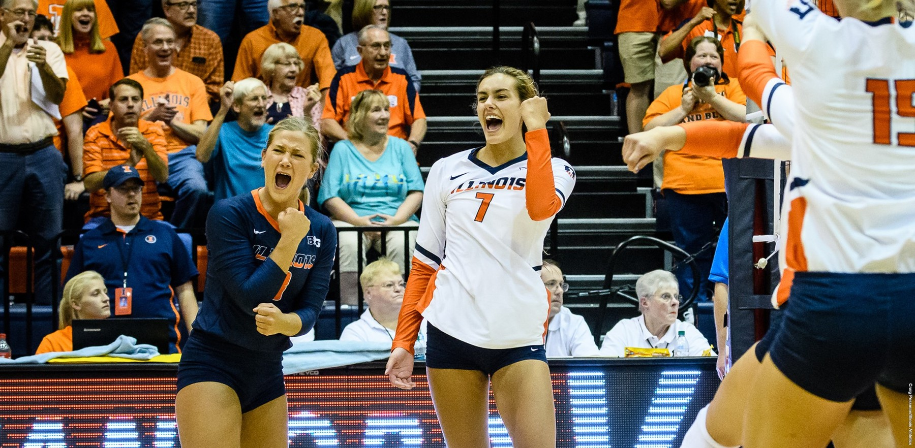 Illini volleyball players raise fists to celebrate a point