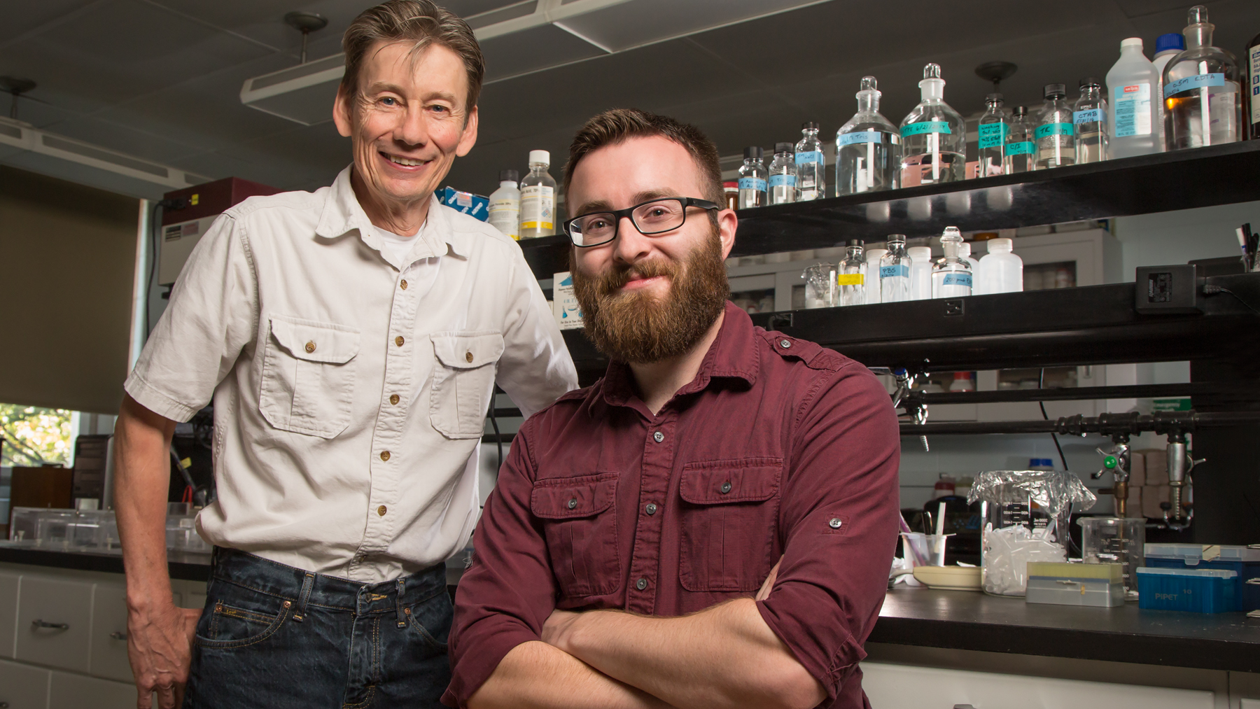 U. of I. professor Ken Paige, standing, and graduate student Miles Mesa study the molecular underpinnings of plant defenses. Photo by Brian Stauffer