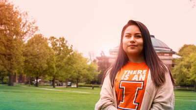 student on the Quad; Foellinger Auditorium background