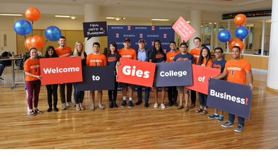 students hold placards announcing the new name of the college