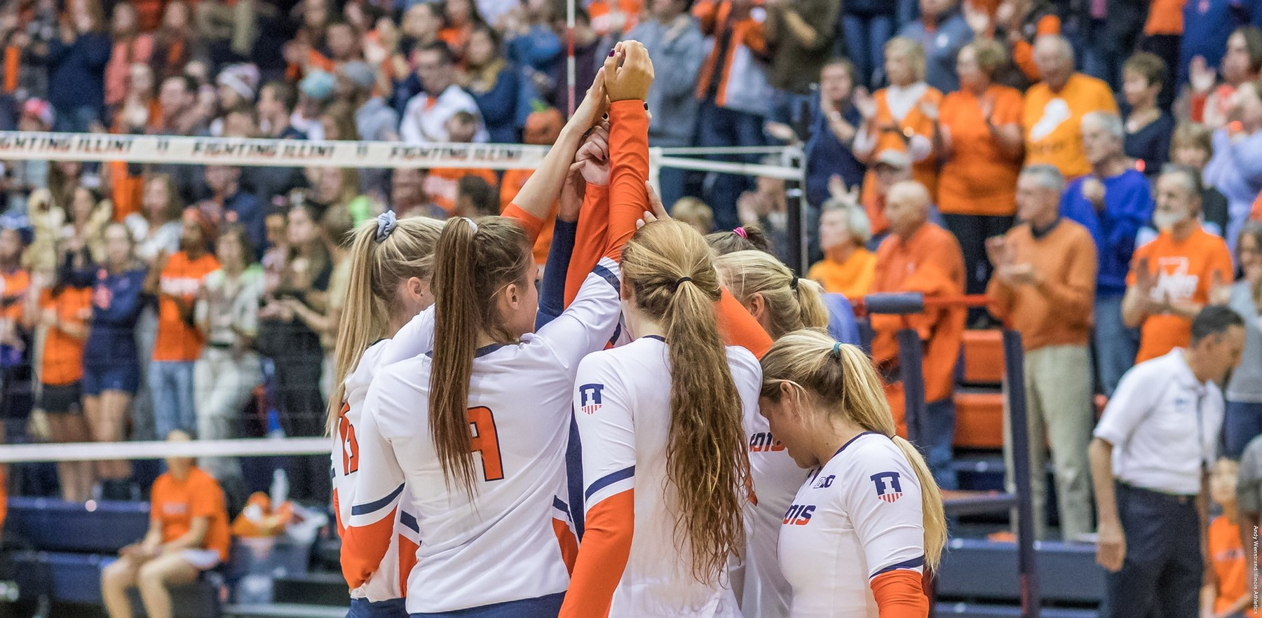 volleyball players huddle on the court