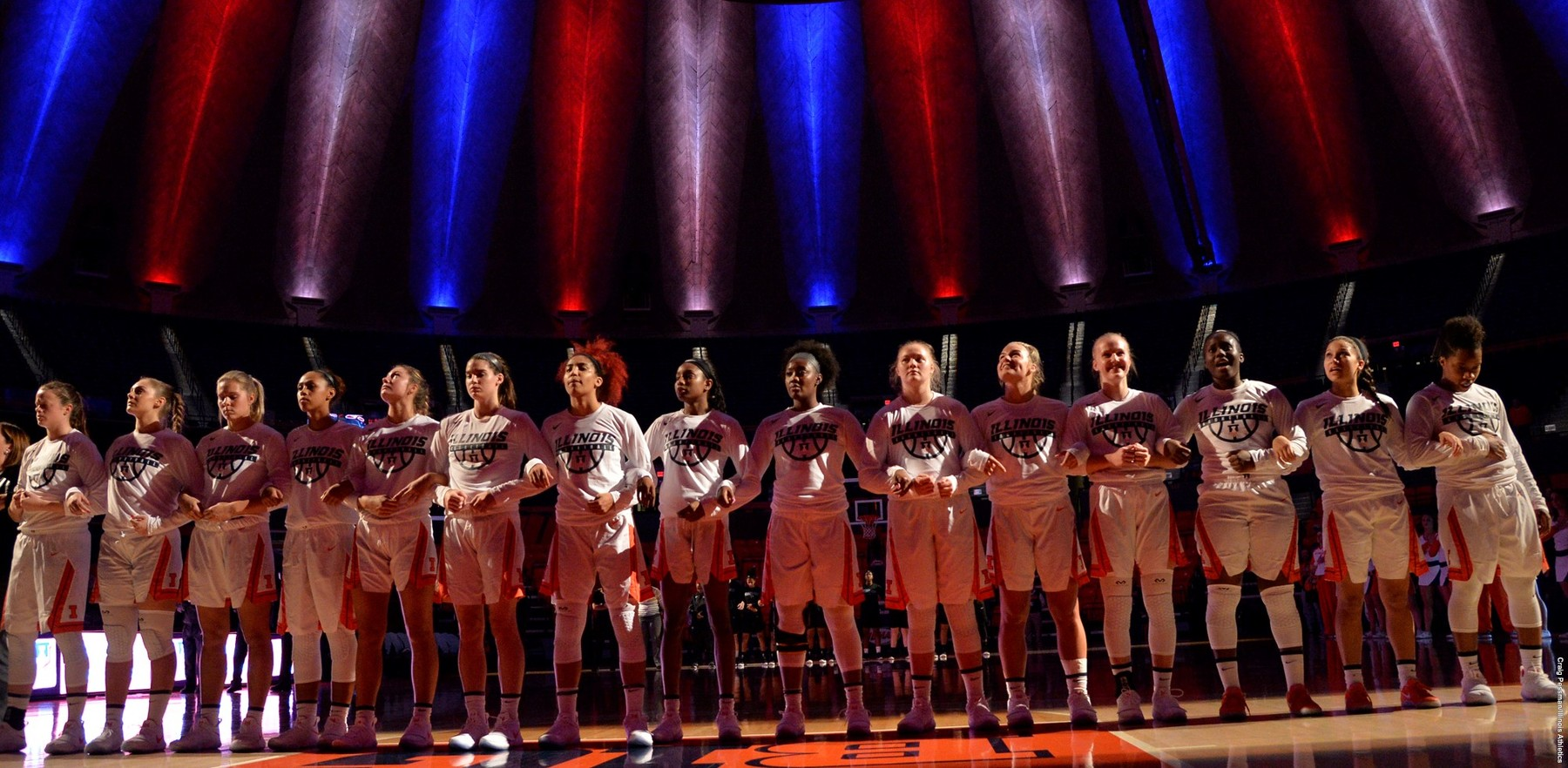 women's basketball team backed by orange and blue lights at state farm center