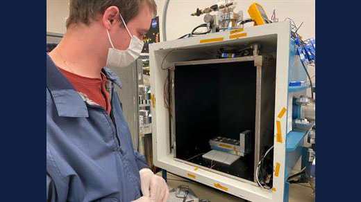 AE graduate student Eric Alpine takes inventory of samples being tested in the Laboratory For Advanced Space Systems at Illinois' thermal vacuum chamber.