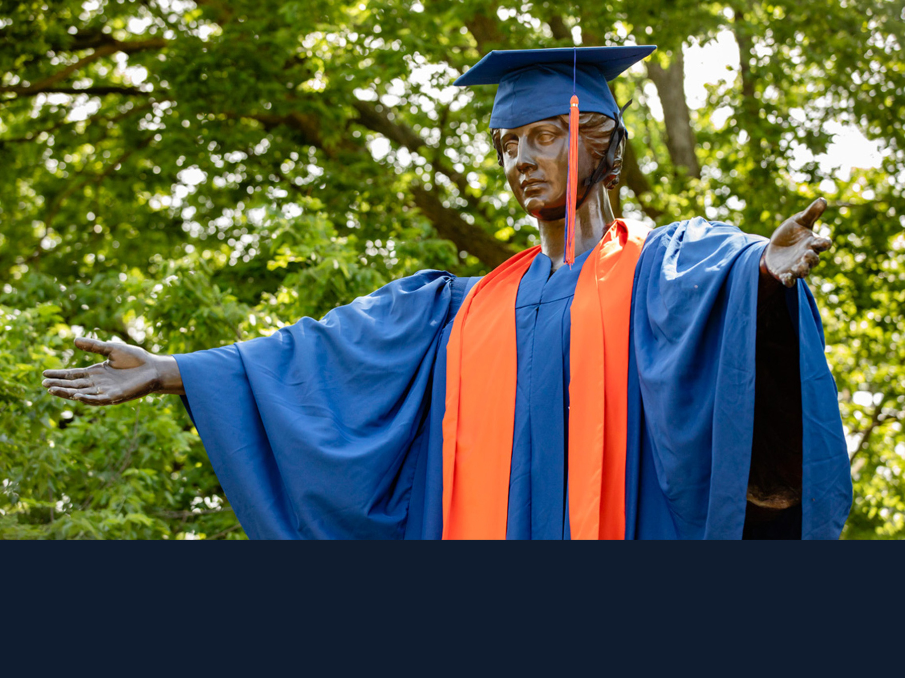 Alma Mater statue dressed in cap and gown