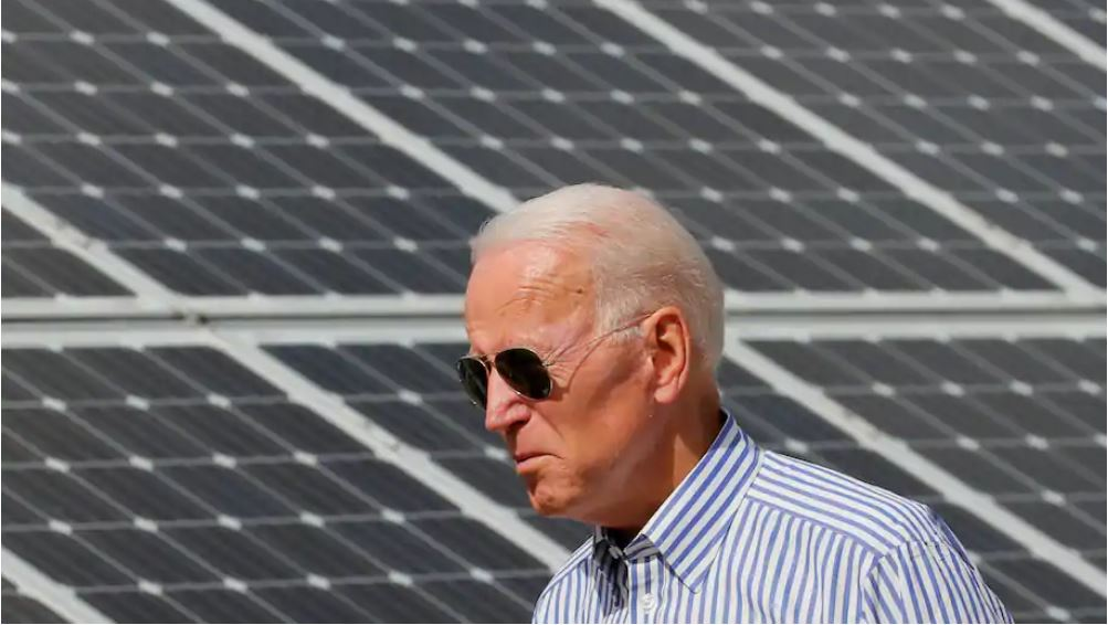 Former vice president Joe Biden walks past solar panels on a tour of the Plymouth Area Renewable Energy Initiative in Plymouth, N.H., in June 2019. (Brian Snyder/Reuters)