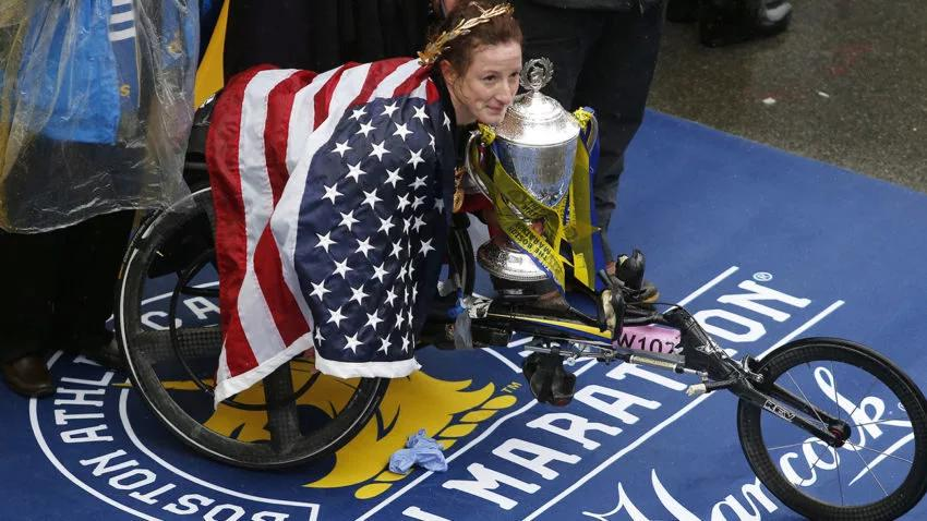 Tatyana McFadden draped in American flag at the Boston Marathon awards ceremoney