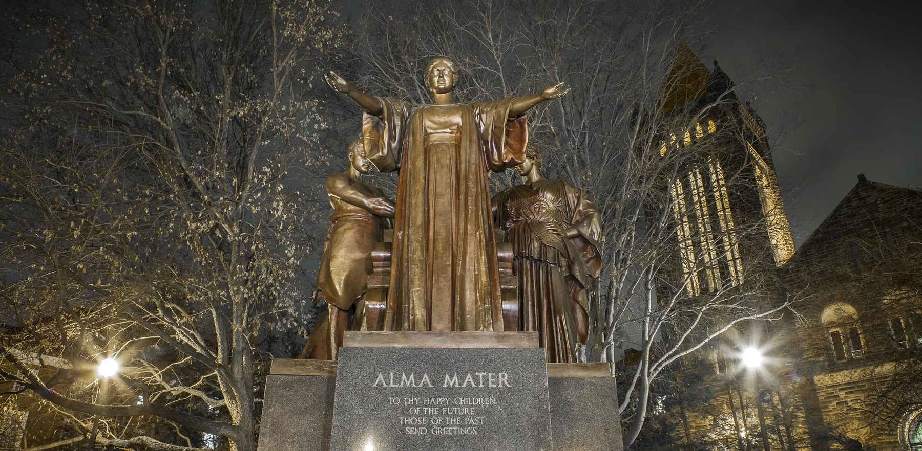 dramatic image of the Alma Mater statue and Algeld Chime Tower at night