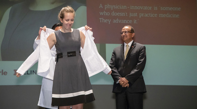 In a July ceremony, Elizabeth Woodburn receives her white coat, signifying that she is a physician-in-training, from dean King Li and executive associate dean Rashid Bashir. Photo by L. Brian Stauffer