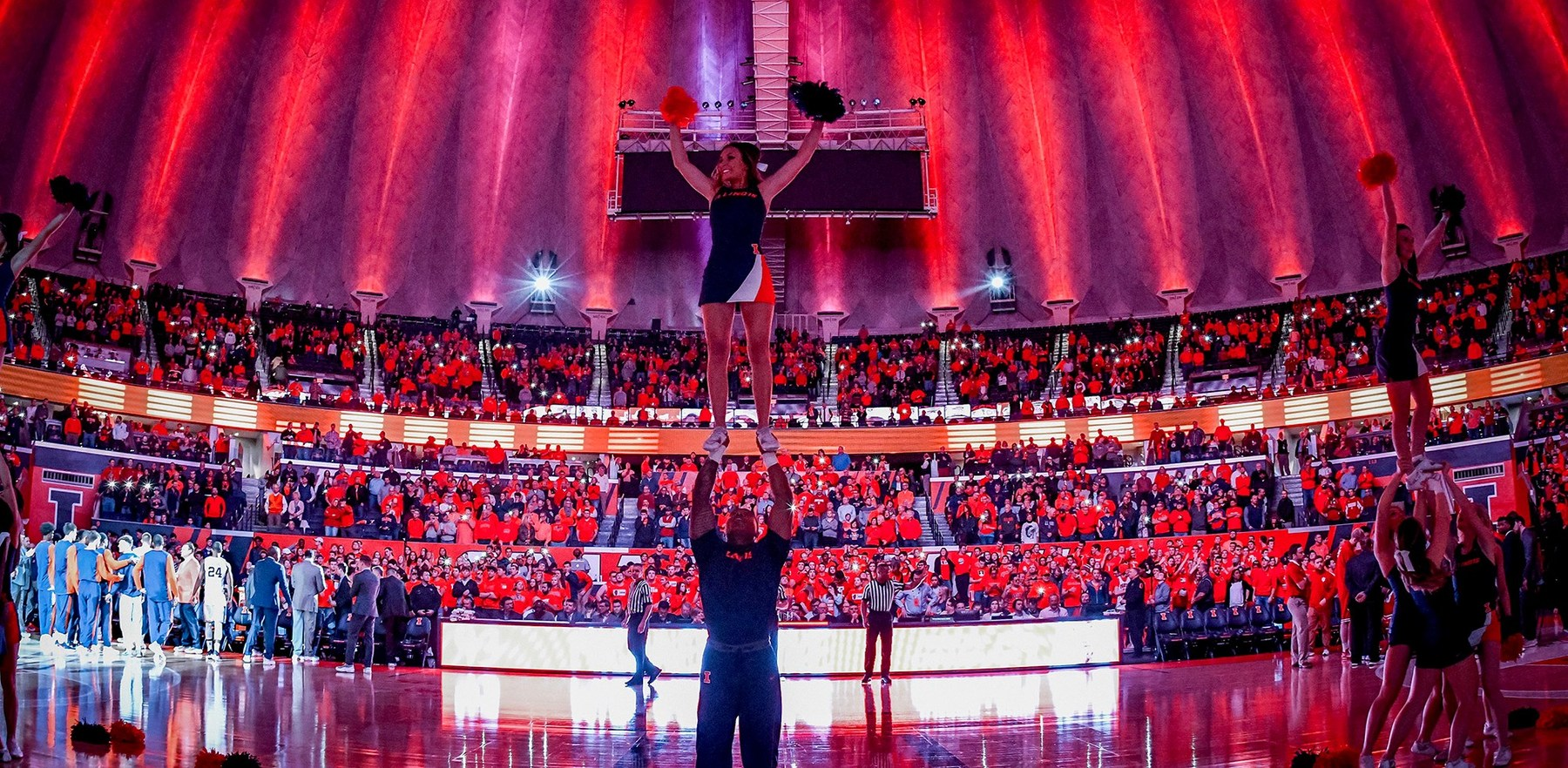 cheerleaders perform before an Illini basketball game in orange-lit State Farm Center