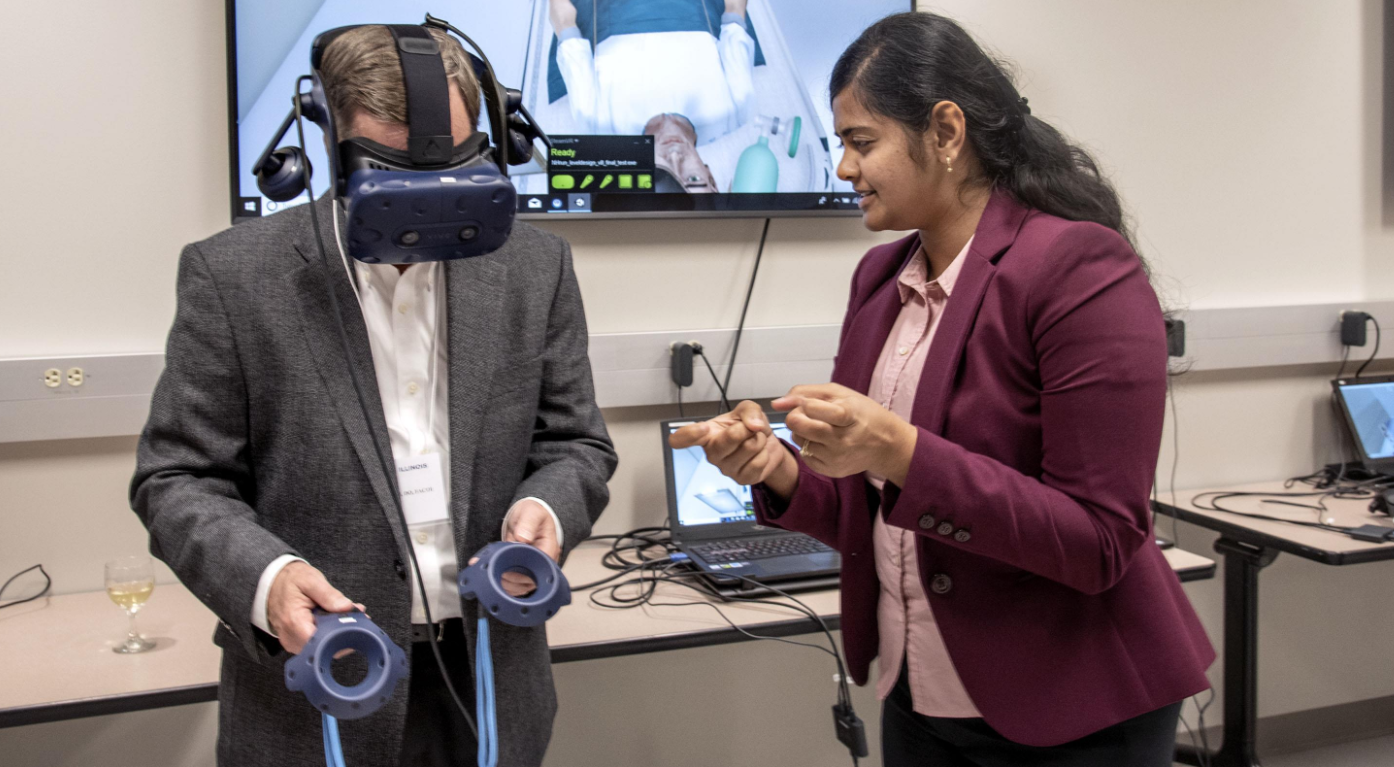 engineer helps guide a visitor through a Virtual Reality demonstration during the Jump Simulation Open House
