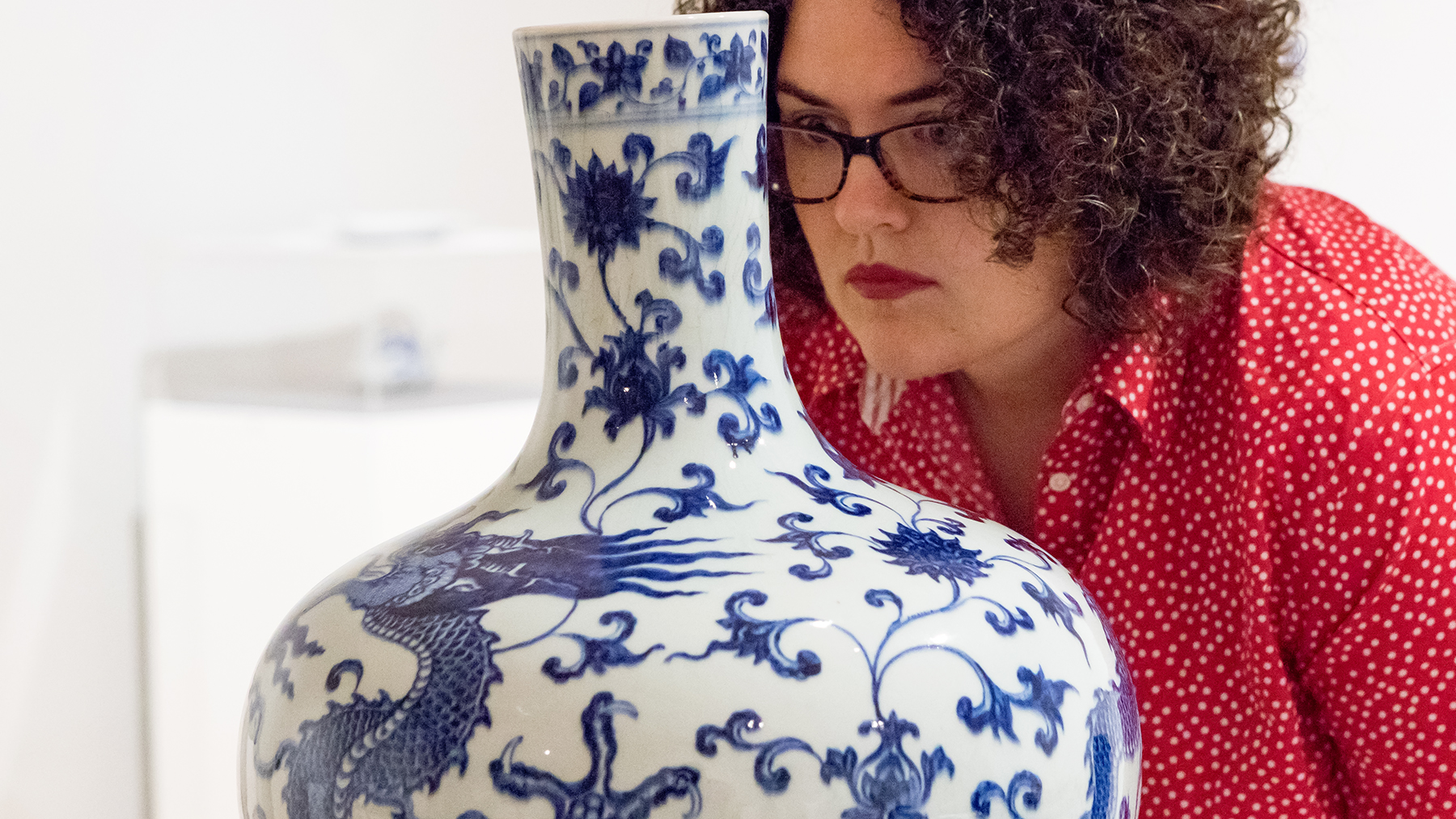 KAM curator Maureen Warren takes a close look at the vase. image by Natalie Fiol