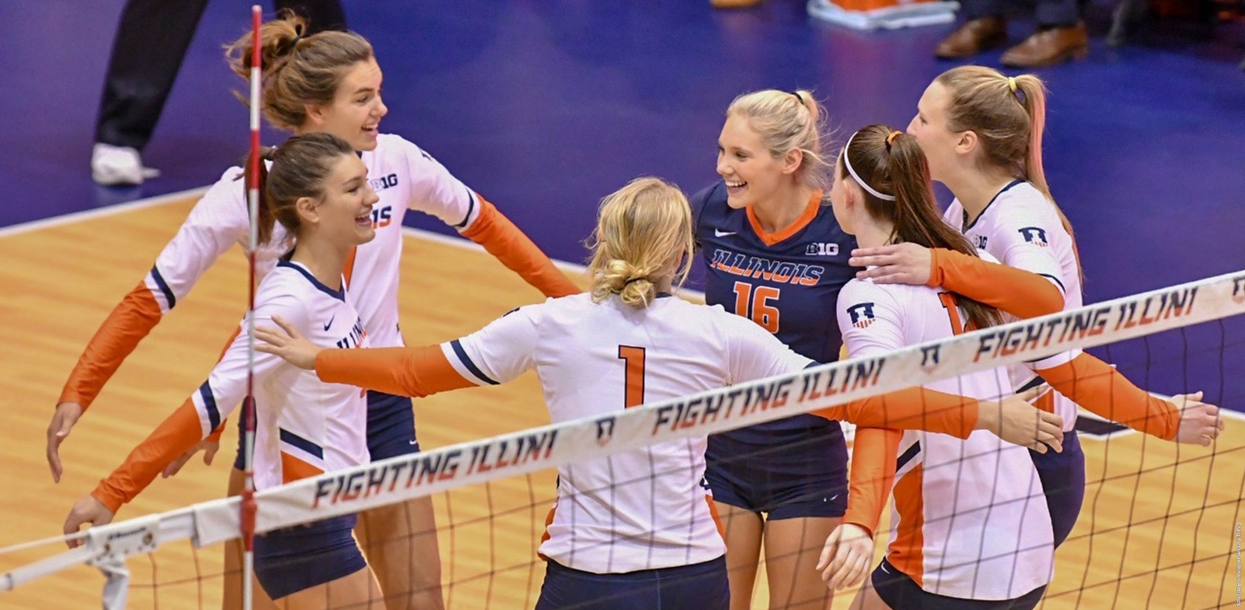 volleyball players' group hug on the court at Huff Hall Wednesday night