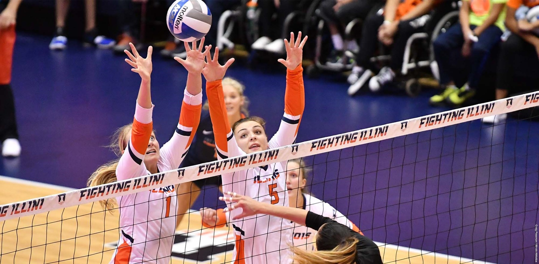 Volleyball players block a shot close to the net