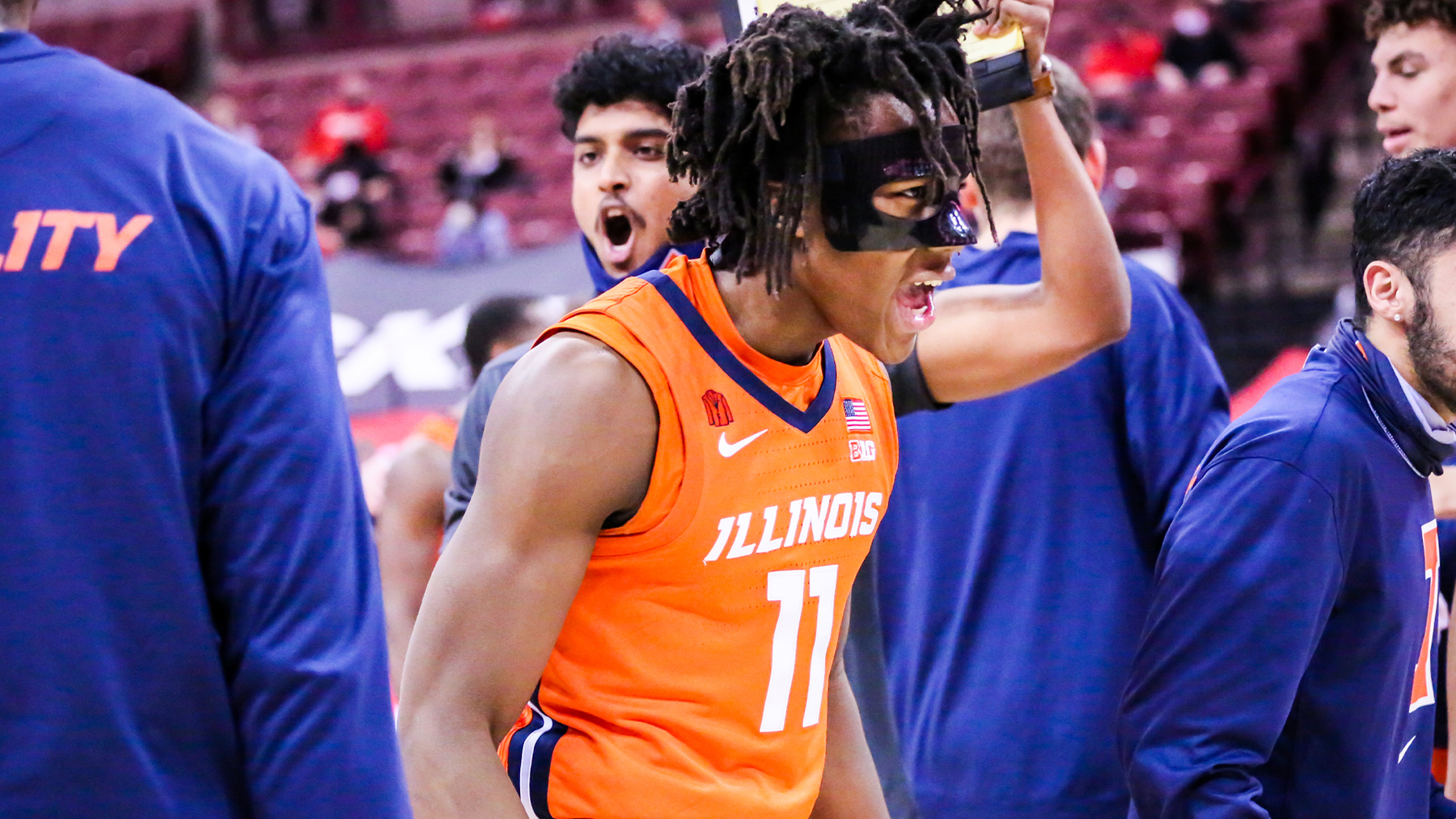 Ayo Dosunmu, wearing a mask to protect a broken nose, with teammates