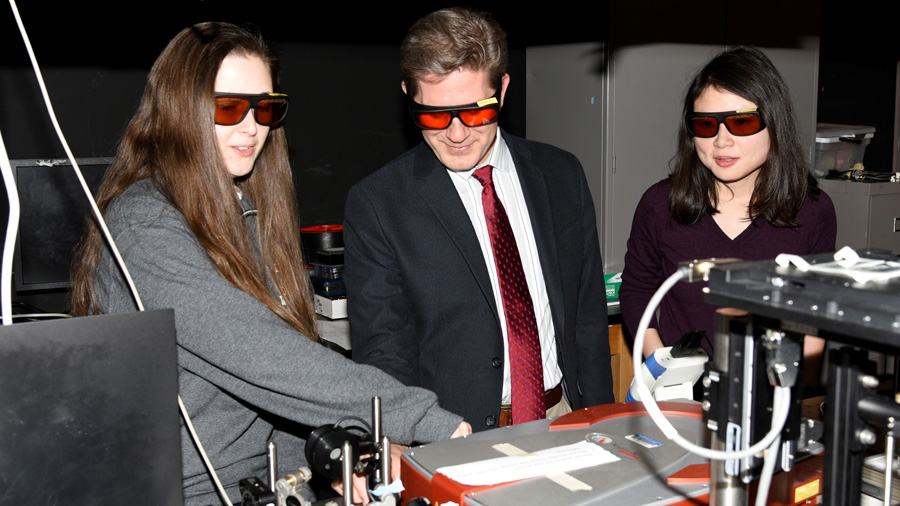 Stephen Boppart, center, wears goggles to view lab work