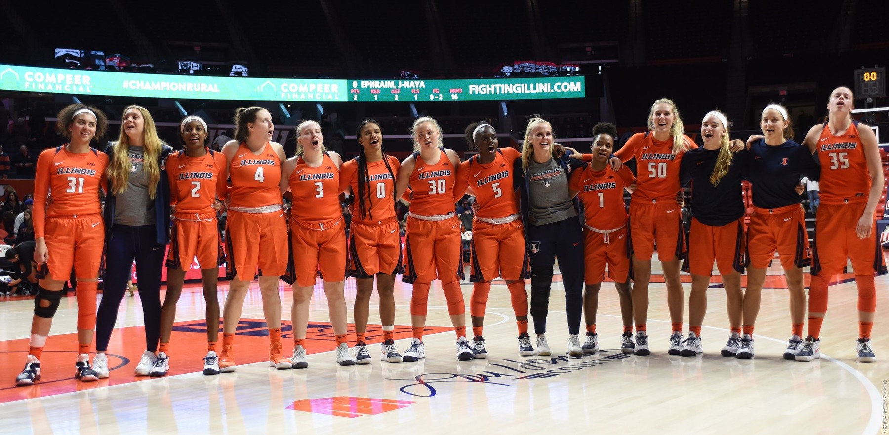 Women's Basketball team with coaches, all arm-in-arm