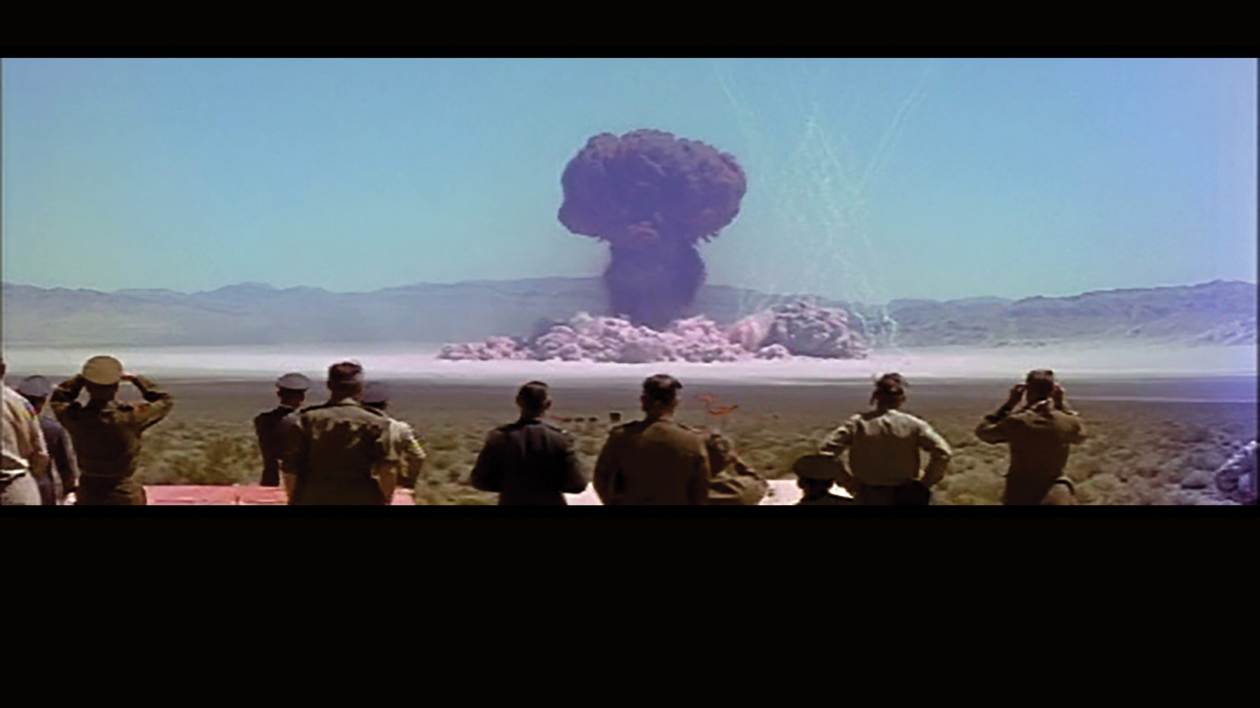 Observers look on during a nuclear test in the Nevada desert in the early 1950s, one of many filmed by a secret Hollywood studio called Lookout Mountain Laboratory. Image from CinemaScope footage from 1955, restored and reconstructed by Peter Kuran. Photo courtesy the Atomic Filmmakers, Santa Clarita, California.