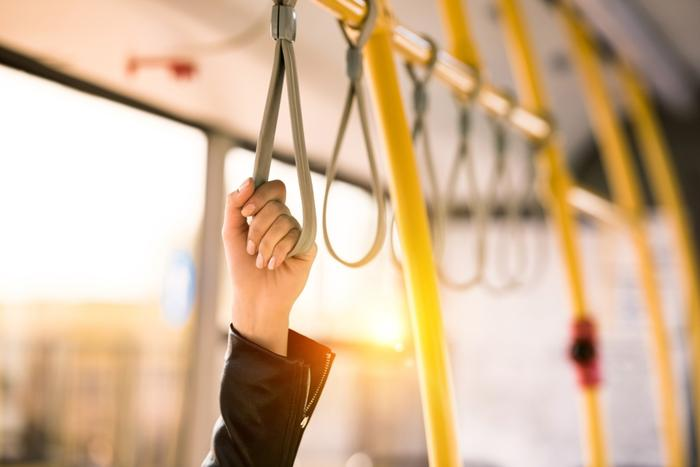 bus rider holds on to overhead strap. photo by LightFieldStudios - Getty Images