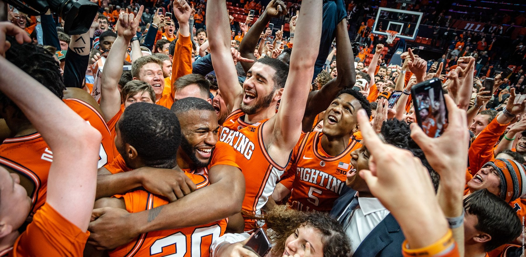 Illini basketball players celebrate, surrounded by fans, who stormed the court followiong the victory over the Spartans