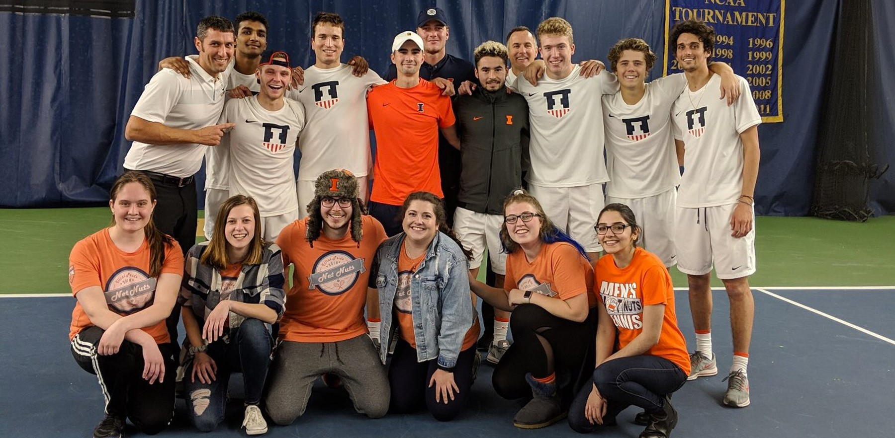 men's tennis team poses with Orange Krush members who traveled to the match