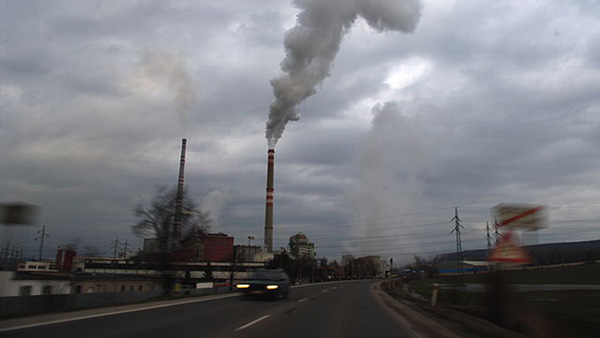 factory billowing pollution from stacks. Photo via Wiki Commons