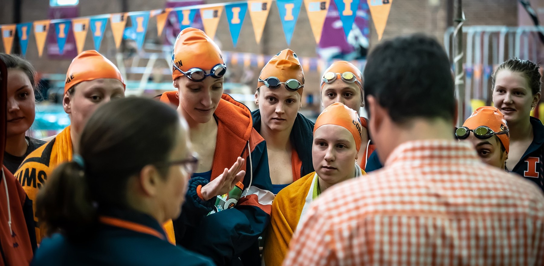 Swimming & Diving team members gather around coaches