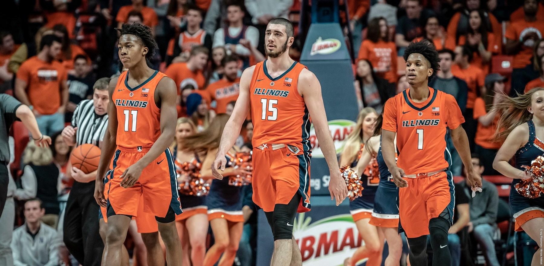 freshman Ayo Dosunmu, sophomore Trent Frazier, and freshman Giorgi Bezhanishvili walk in tandem across a basketball court