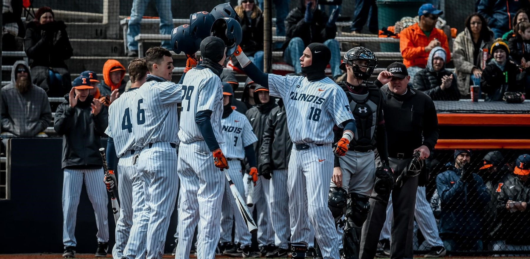 Illini baseball players celebrate Sunday's win with surrounding fans bundled against the cold
