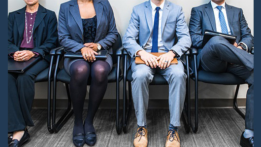 stock image of four job applicants dressed in suits sitting in adjacent chairs