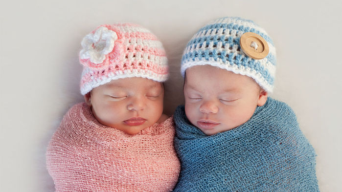 Twin babies side-by-side. Photo by OH BABY PRODUCTIONS/ALAMY STOCK PHOTO