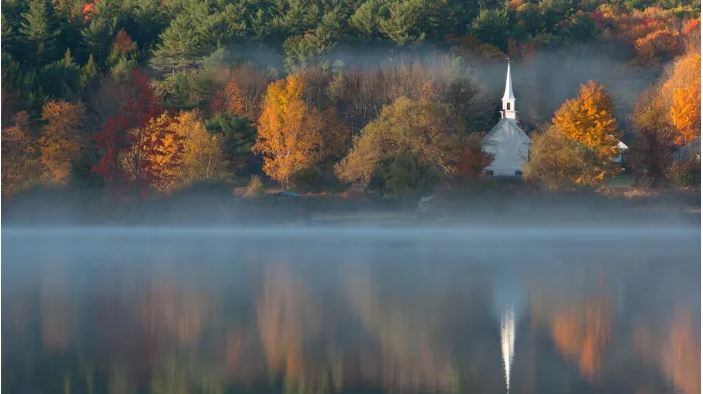 white, steepled church amoungst trees, as seen from across a lake. Stock photo by Peter Lewis/Unsplash