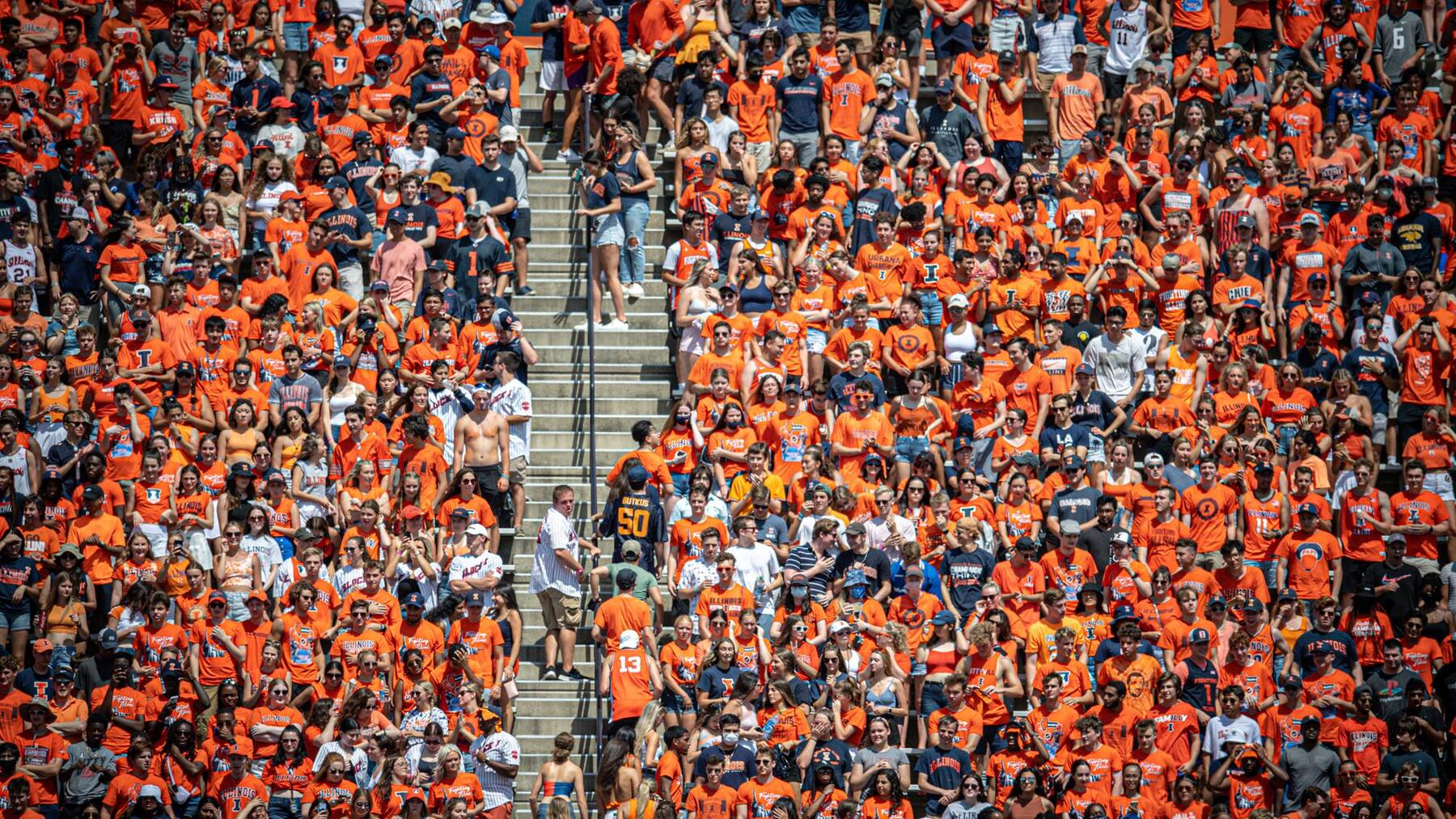 a crowd, nearly all dressed in orange, watch an Illini football game pre-COVID