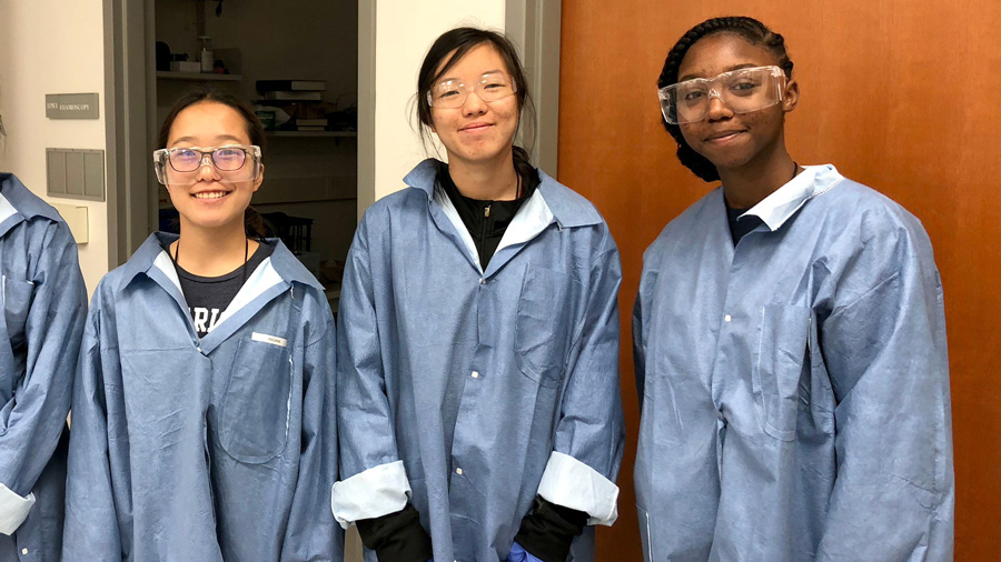 Participants in the 2018 Girls Learning Electrical Engineering (GLEE) camp wearing lab coats and googles.