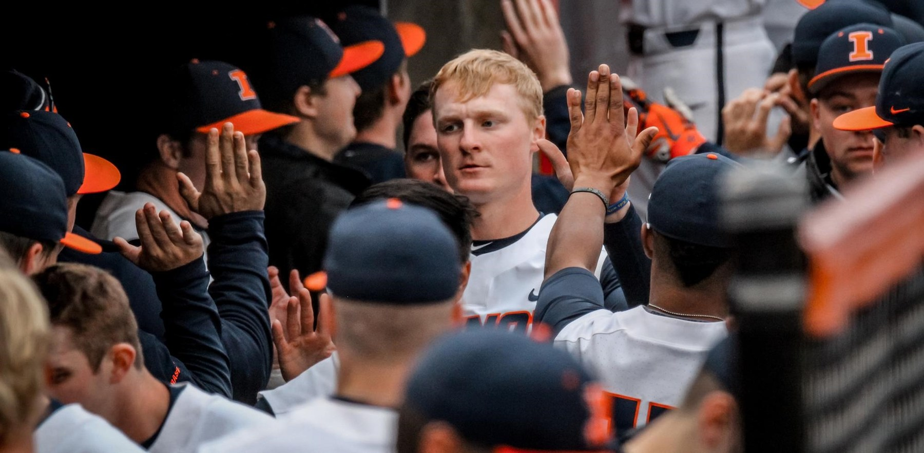 Illini baseball players exchange 'high fives' in the dugout