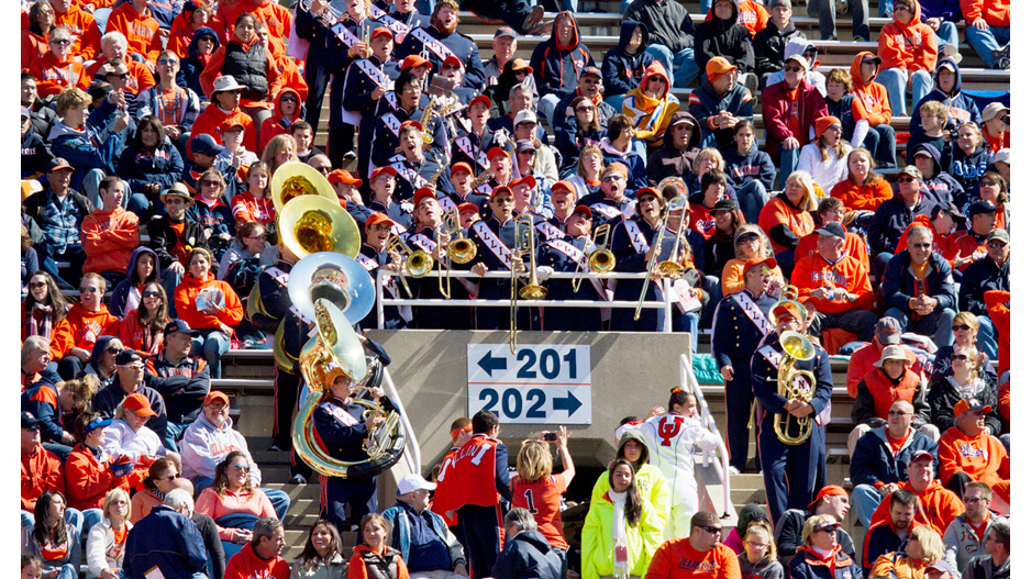football crowd at Memorial Stadium with Marching Illini brass players standing
