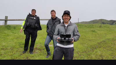 Elias Waddington, holding remote control, and co-workers during a search and rescue flight.