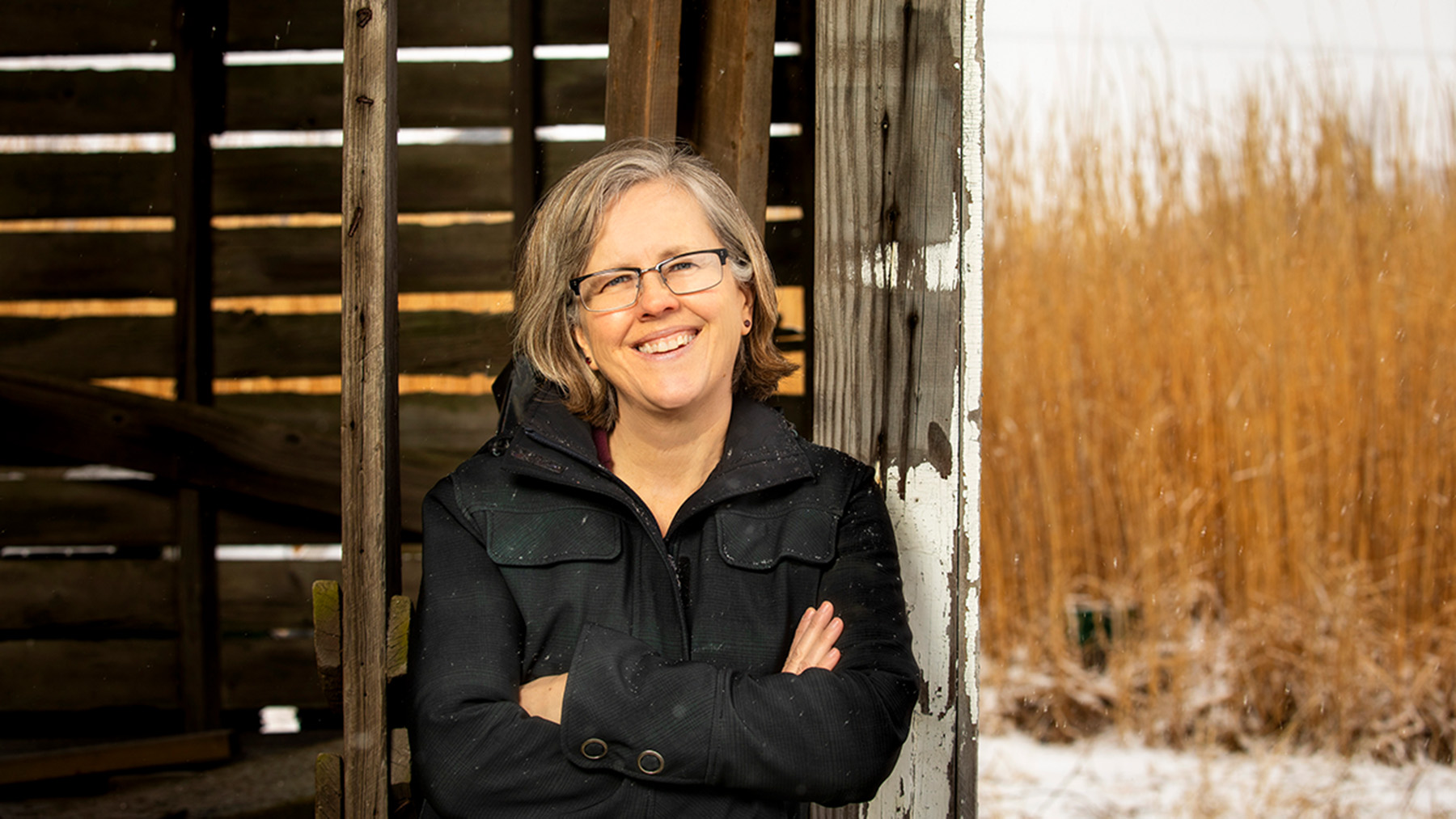 Professor, author Kristin Hoganson shown standing in a farm shed. Photo by Fred Zwicky